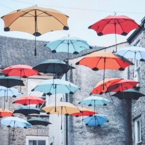 A photograph of colourful umbrellas suspended in the air with stone houses in the background by a Koestler Awards entrant from Ann House.